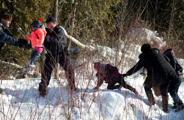 FILE PHOTO --  Royal Canadian Mounted Police (RCMP) officers assist a child from a family that claimed to be from Sudan as they walk across the U.S.-Canada border into Hemmingford, Canada, from Champlain in New York, U.S., February 17, 2017. REUTERS/Christinne Muschi/File Photo