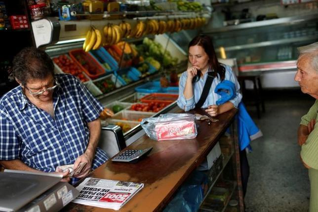 3月20日、チリのバチェレ大統領はトランプ米大統領と19日に電話会談を行ったと記者団に明らかにした。トランプ氏は、ベネズエラの政治的、人道的状況について懸念を示したという。写真はベネズエラ首都カラカスのスーパーマーケットで紙幣を数える様子。9日撮影(2017年 ロイター/Carlos Garica Raslins)