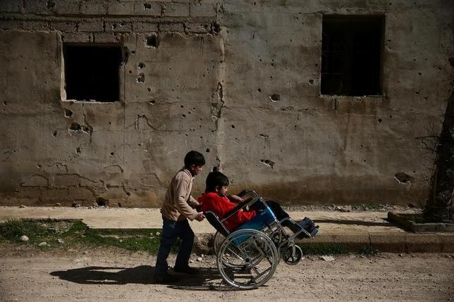 3月15日、シリア首都ダマスカス近郊の東グータ地区にある反体制派の主要拠点となっているドゥーマが空爆されるようになり、まひを患う14歳のジアド君(右)は自室に独りで閉じこもりがちだという。2月撮影(2017年 ロイター/Bassam Khabieh)