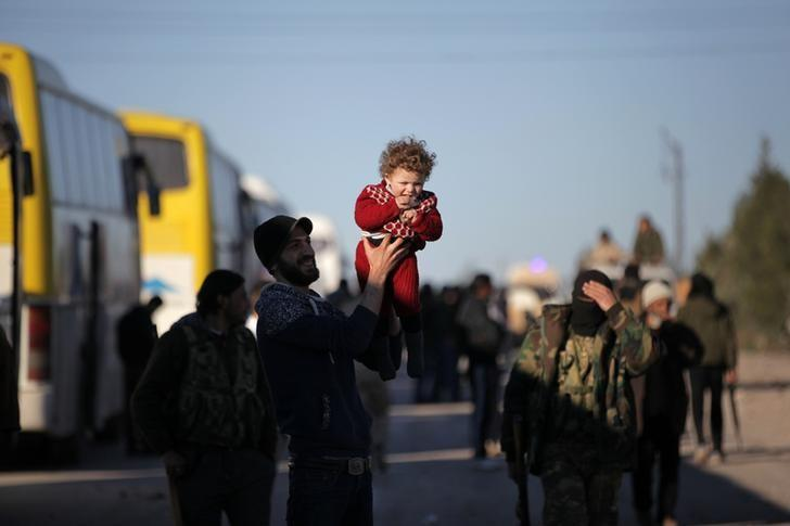 Rebel fighters and their families that evacuated the besieged Waer district in the central Syrian city of Homs, after an agreement reached between rebels and Syria's army, arrive on the southern outskirts of the Syrian city of al-Bab, Syria March 19, 2017. REUTERS/Khalil Ashawi