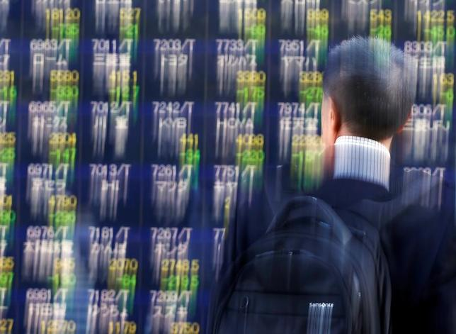 3月24日、東京株式市場で日経平均は、続伸となった。為替が1ドル110円台後半まで円高に振れたことで、朝方は主力輸出株に売りが先行した。写真は都内で為替ボードと眺める男性。昨年11月撮影(2017年 ロイター/Issei Kato)