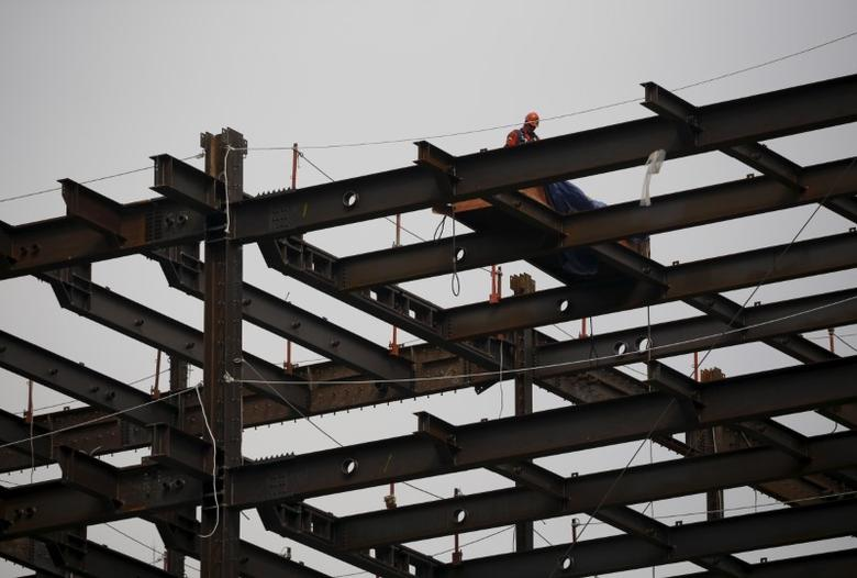 A worker stands on a steel beam at a construction site in central Seoul, South Korea, March 25, 2016.  REUTERS/Kim Hong-Ji
