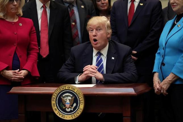 3月27日、トランプ米大統領は、オバマ前政権が導入した一連の環境規制を撤回する大統領令に署名する。国内のエネルギー生産拡大を目指すが、環境保護団体は法廷で戦う姿勢を示している。ホワイトハウスでの法案の調印式で撮影(2017年 ロイター/Carlos Barria)