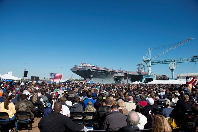 3月2日、トランプ米大統領は、国防支出の増額計画を自画自賛する演説の舞台として、建造に約1兆5000億円を費やした米海軍の最新鋭航空母艦「ジェラルド・R・フォード」の甲板を選んだ。写真は2013年11月、バージニア州での同空母の命名式に集まった人々。米海軍提供(2017年 ロイター)