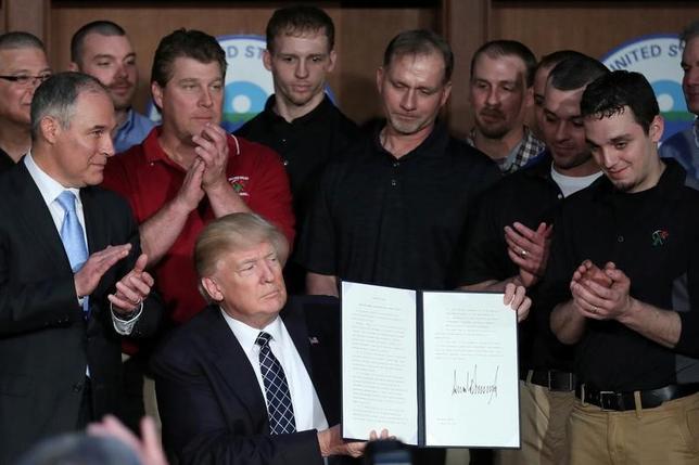 3月28日、トランプ米大統領は、オバマ前政権が導入した一連の環境規制を撤廃する大統領令に署名した。写真は28日、ワシントンで大統領令に署名するトランプ氏(2017年 ロイター/Carlos Barria )