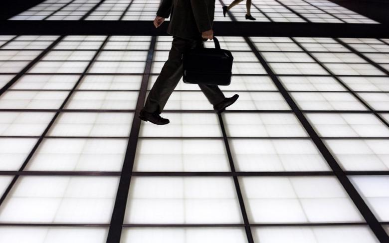 People cross an illuminated floor at a banking district in central Tokyo November 27, 2014.  REUTERS/Thomas Peter/File Photo