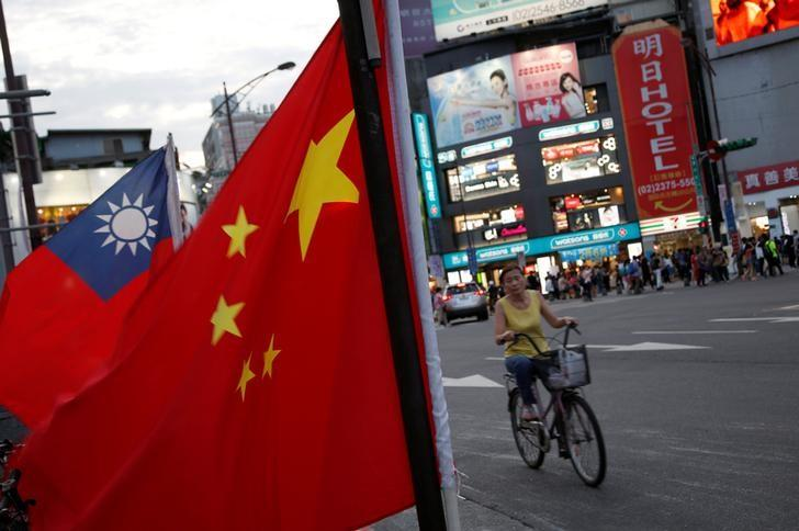 A woman rides a bike past Taiwan and China national flags during a rally held by a group of pro-China supporters calling peaceful reunification, 6 days before  the inauguration ceremony of President-elect Tsai Ing-wen, in Taipei, Taiwan May 14, 2016. REUTERS/Tyrone Siu/File Photo