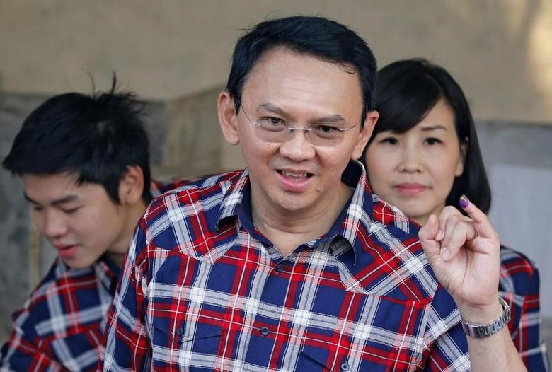 Governor of Indonesia's capital Basuki Tjahaja Purnama (C) shows his ballot as he stands beside his son Nicholas Sean Purnama (L) and his wife Veronica Tan during an election for Jakarta's governor in Jakarta, Indonesia, February 15, 2017. REUTERS/Beawiharta/File Photo