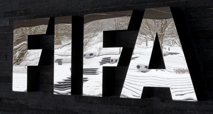 The snow-covered landscape is reflected in a logo in front of FIFA headquarters in Zurich, Switzerland, January 10, 2017. REUTERS/Arnd Wiegmann/Files