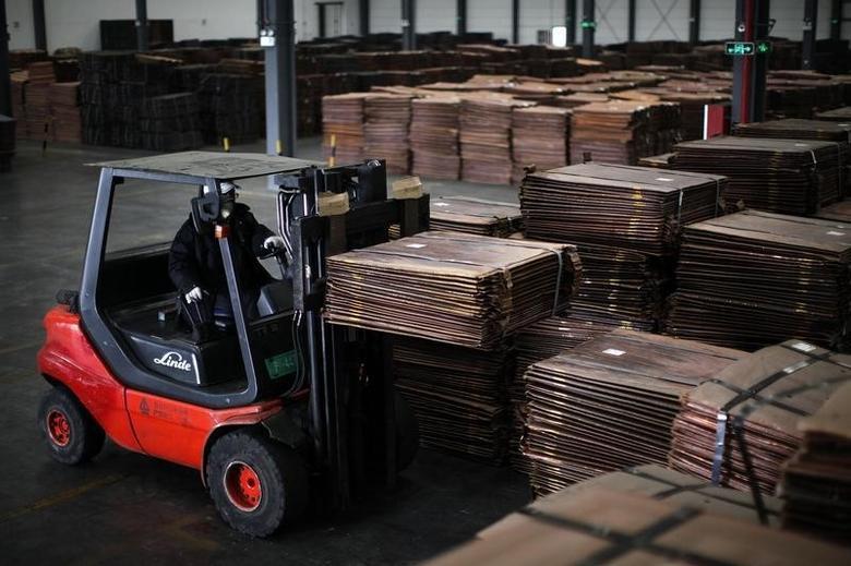 资料图片:2012年3月,上海洋山港附近一处仓库,一名工人驾驶叉车搬运铜板材。REUTERS/Carlos Barria