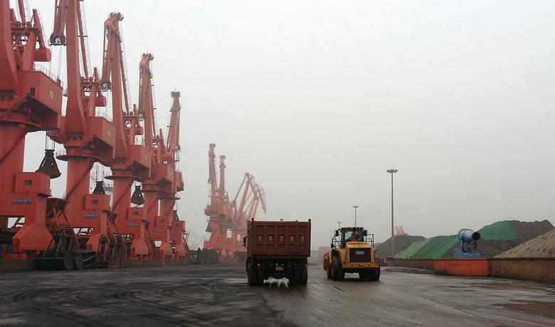 FILE PHOTO: Trucks drive inside an iron ore dump site at the Huanggang Terminal of Qingdao Port, in Qingdao, Shandong province June 7, 2014.  REUTERS/Fayen Wong/File Photo