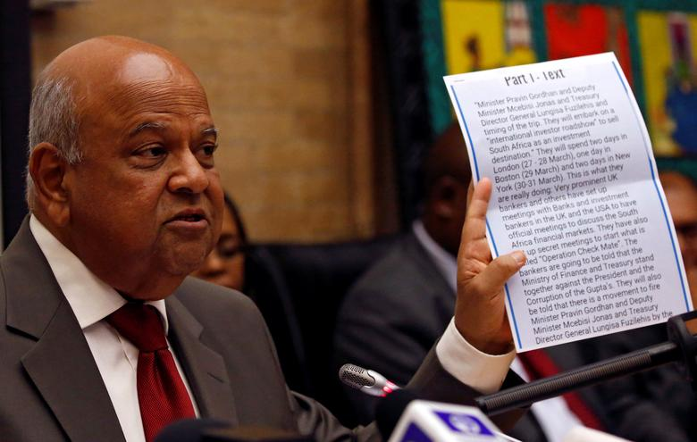 FILE PHOTO - South Africa's outgoing Finance Minister Pravin Gordhan holds a copy of an intelligence report that President Jacob Zuma used as justification to fire him, during a media briefing at their offices in Pretoria, South Africa, March 31,2017. REUTERS/Siphiwe Sibeko