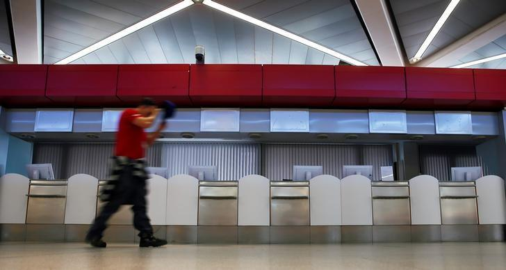 A man passes closed counters during a warning strike by ground services, security inspection and check-in staff at Tegel airport in Berlin, Germany March 13, 2017. REUTERS/Hannibal Hanschke
