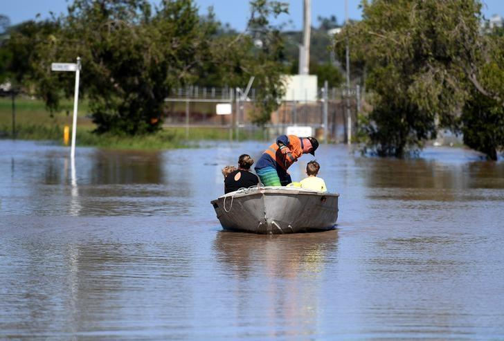 A family uses a boat to get to their house through floodwaters created by Cyclone Debbie in Rockhampton, Australia, April 4, 2017.    AAP/Dan Peled/via REUTERS