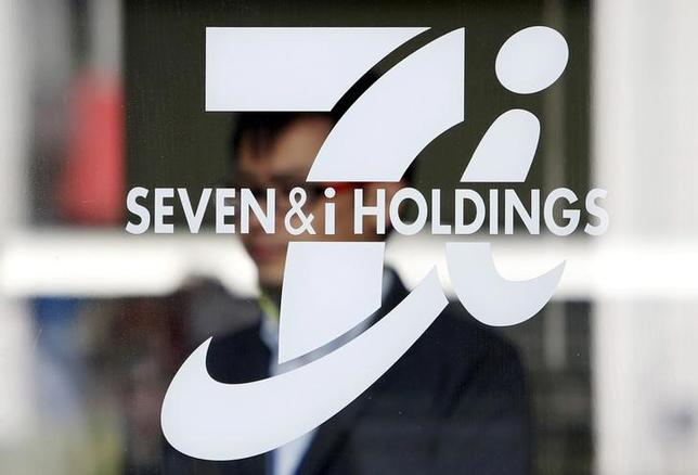FILE PHOTO: A shopper is seen behind a Seven & I Holdings' logo at a 7-Eleven convenience store in Tokyo, Japan, April 6, 2016. REUTERS/Yuya Shino/File Photo