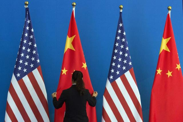FILE PHOTO - A Chinese woman adjusts a Chinese national flag next to U.S. national flags before a Strategic Dialogue expanded meeting, part of the U.S.-China Strategic and Economic Dialogue (S&ED) held at the Diaoyutai State Guesthouse in Beijing, July 10, 2014. REUTERS/Ng Han Guan/Pool