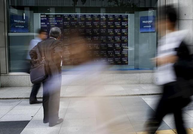 4月10日、東京株式市場で日経平均は終値が始値を下回り、日足は3月30日以来、8営業日連続で「陰線」となった。写真は株価ボードを眺める男性。都内で2015年10月撮影(2017年 ロイター/Toru Hanai)