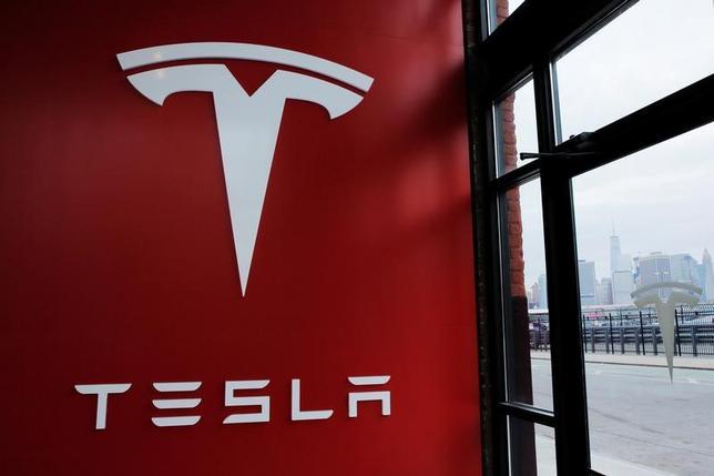 4月10日、米株式市場で電気自動車(EV)メーカーのテスラが終値としての過去最高値を更新し、時価総額でゼネラル・モーターズ(GM)を抜いて米自動車業界の首位に立った。写真はテスラのロゴ。NY市で昨年4月撮影(2017年 ロイター/Lucas Jackson)