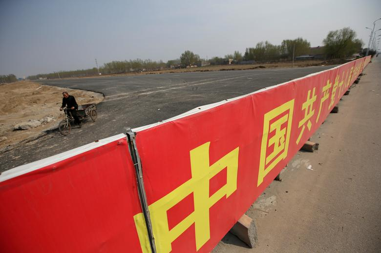 FILE PHOTO: A banner supporting the Communist Party of China is placed at the end of a new road on the outskirts of Rongcheng county, one part of the new special economic zone Xiong'an New Area, Hebei province, China April 3, 2017. REUTERS/Jason Lee/File Photo