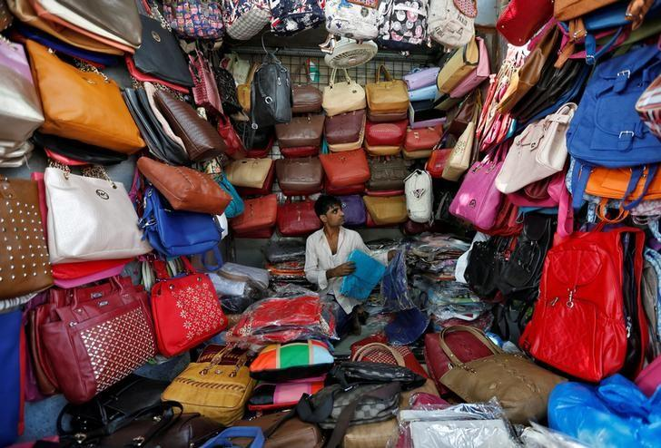 FILE PHOTO -  A vendor arranges bags as he waits for customers at his shop at a market in Mumbai, India, January 6, 2017. REUTERS/Danish Siddiqui/File Photo