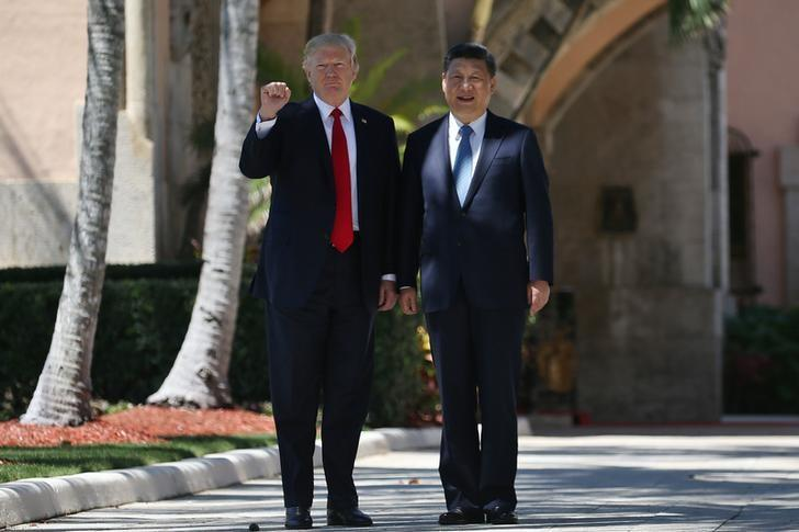 U.S. President Donald Trump and China's President Xi Jinping are seen during a walk along the front patio of the Mar-a-Lago estate after a bilateral meeting in Palm Beach, Florida, U.S., April 7, 2017. REUTERS/Carlos Barria