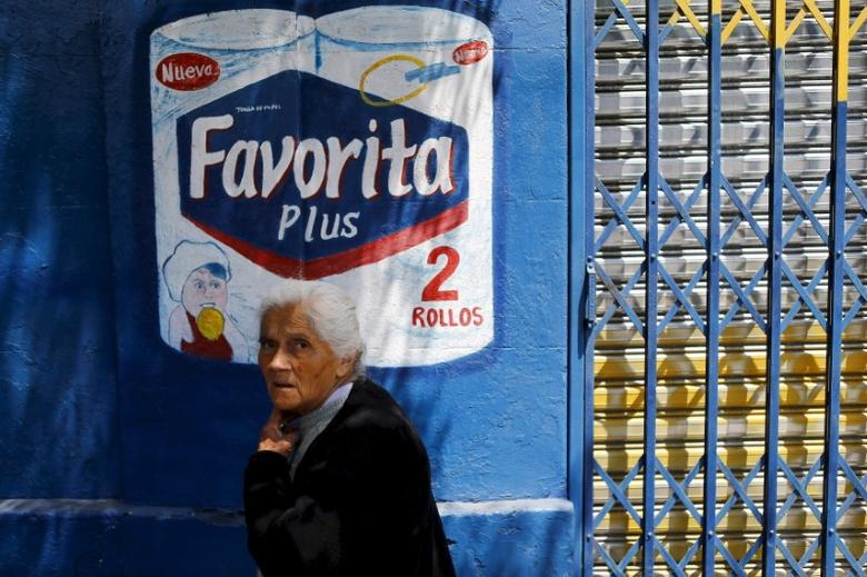 A woman walks past an advertisement of a tissue paper brand of Swedish SCA company on a street in Santiago, Chile, November 10, 2015.  REUTERS/Ivan Alvarado/File Photo