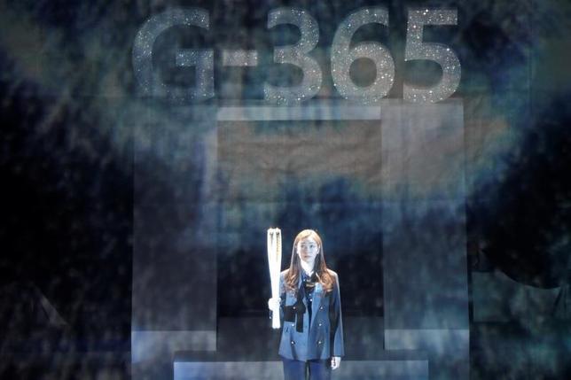 4月17日、2018年平昌冬季五輪の組織委員会は、11月に聖火リレーをスタートさせると発表。韓国国内で7500人が2018キロのルートをつなぐという。写真は聖火を持つ元フィギュアスケート選手のキム・ヨナさん。韓国の平昌で2月撮影(2017年 ロイター/Kim Hong-Ji)