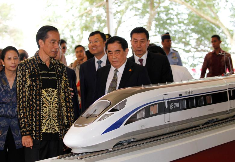FILE PHOTO: Indonesian President Joko Widodo (2nd L) and the general manager of China Railway Corp. Sheng Guangzu (C) stand next to a train model as they attend a groundbreaking ceremony for the Jakarta-Bandung fast-train railway line in Walini, West Java province, Indonesia January 21, 2016. REUTERS/Garry Lotulung/File Photo