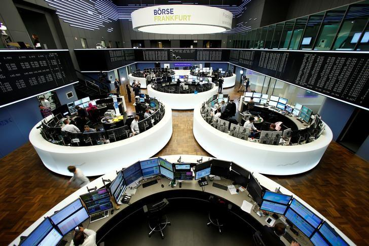 Traders work at their desks in front of the German share price index, DAX board, at the stock exchange in Frankfurt, Germany, February 28, 2017. REUTERS/Staff/Remote