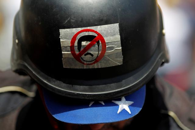 An opposition demonstrator wears a helmet with a sticker representing Venezuela's President Nicolas Maduro during a rally against him in Caracas, Venezuela, April 20, 2017. REUTERS/Christian Veron