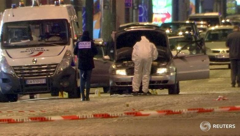 A still image from video footage shows Police investigators inspect the car used by the attacker on the Champs Elysees Avenue after a policeman was killed and two others were wounded in a shooting incident in Paris, France, April 20, 2017.    REUTERS/Reuters Tv - RTS13871