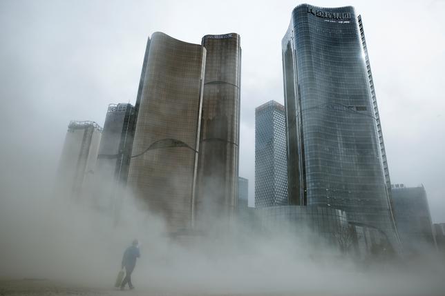 4月21日、中国の環境保護省(MEP)は、環境問題対策の一環で調査した中国企業のうち、3分の2以上が環境規則に違反していたと発表した。写真は風により埃が舞い上がる建築中のオフィス街。北京で20日撮影(2017年 ロイター/THOMAS PETER)