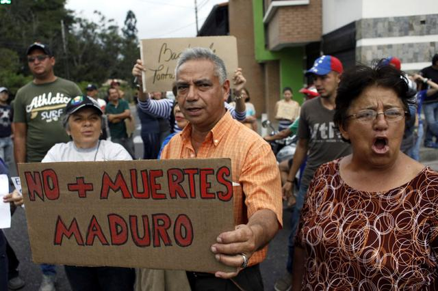 People holding a placard that reads ''No more deaths, Maduro'' gather outside the wake of Paola Ramirez, a student who died during a protest, in San Cristobal, Venezuela, April 20, 2017. REUTERS/Carlos Eduardo Ramirez