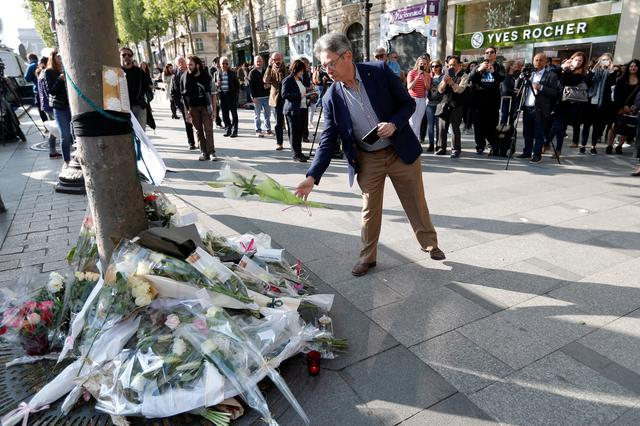 A man leaves flowers on the Champs Elysees Avenue the day after a policeman was killed and two others were wounded in a shooting incident in Paris, France, April 21, 2017.   REUTERS/Charles Platiau