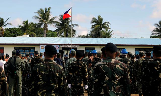 A Philippine flag flutters in Philippine occupied (Pagasa) Thitu island, in disputed South China Sea, as soldiers and civilians sing the country's national anthem April 21, 2017. REUTERS/Erik De Castro
