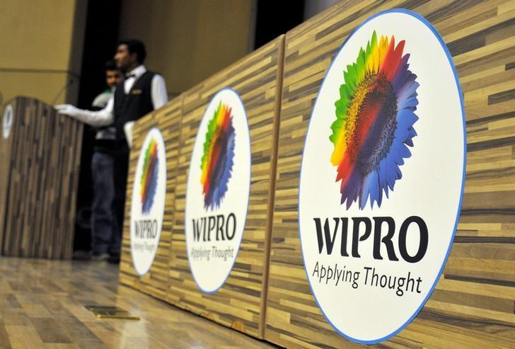 Stewards are seen behind desks with the logo of India's third-largest software services firm Wipro Ltd inside the company's headquarters in Bengaluru, India, October 21, 2016. REUTERS/Abhishek N. Chinnappa/File Photo