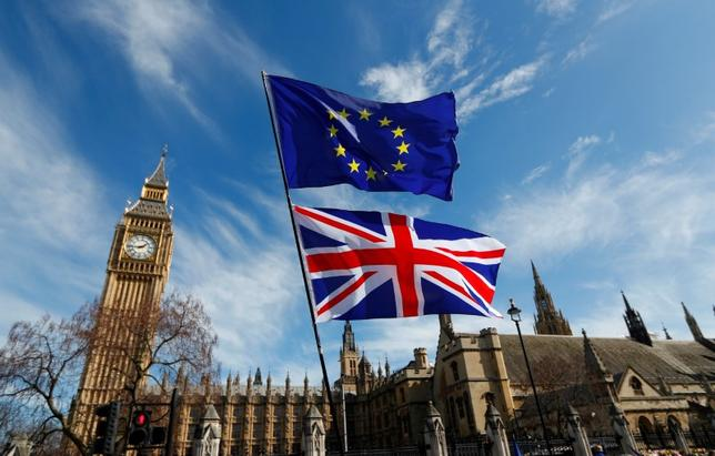4月25日、欧州連合(EU)は英国のEU離脱(ブレグジット)に向けた交渉で、離脱前に英国に入国し、5年居住したEU市民に対する永住権付与など、英国で暮らすEU市民の権利保護を強く求める見通しだ。写真のEU旗(下段)と英国旗(上段)はロンドン国会議事堂前で3月撮影(2017年 ロイター/Peter Nicholls)