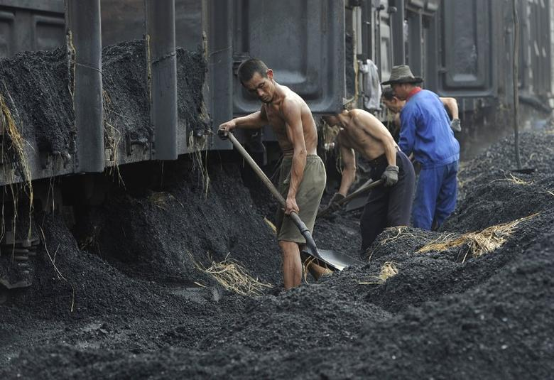 Labourers shovel coal at a coal storage site in Hefei, Anhui province July 21, 2011.  REUTERS/Stringer