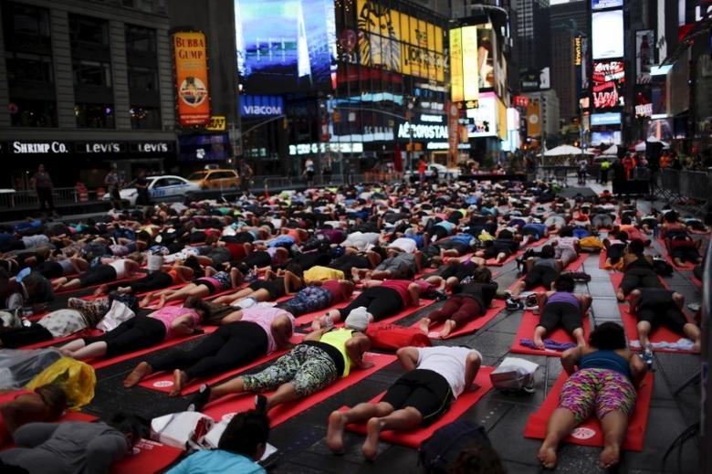 People practice yoga in Times Square as part of a Summer Solstice and International Day of Yoga celebration in New York June 21, 2015. REUTERS/Eduardo Munoz