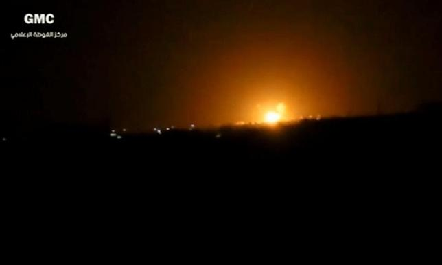 A still image taken from a video posted to a social media website and said to be shot on April 27, 2017, shows explosions and rising flames amid lights in distance, said to be shot in Damascus, Syria. Social Media Website via Reuters TV