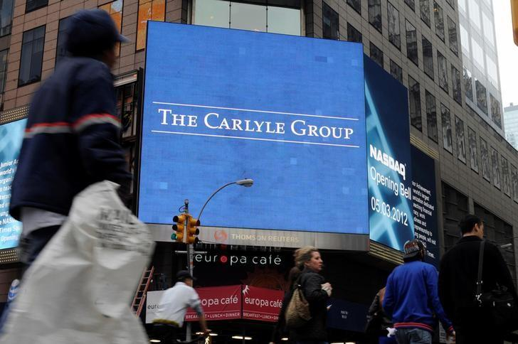 File Photo: Passersby walk in front of video monitors announcing the Carlyle Group's listing on the NASDAQ market site in New York's Times Square after the opening bell for trading, U.S. May 3, 2012. REUTERS/Keith Bedford/File Photo