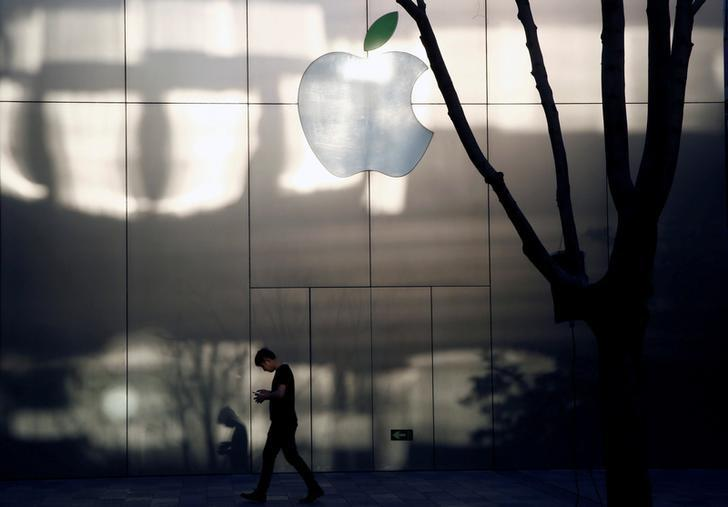 A man uses his phone as he walks past an Apple store in Beijing, China on April 25, 2017. REUTERS/Thomas Peter/Files