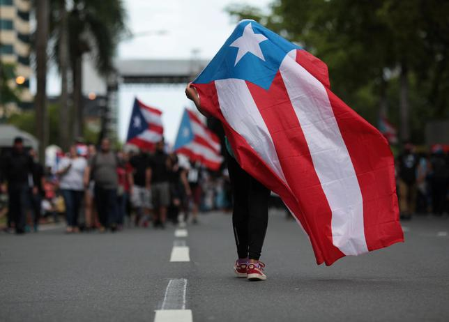 A person carries a Puerto Rican national flag during a protest against the government's austerity measures as Puerto Rico faces a deadline on Monday to restructure its $70 billion debt load or open itself up to lawsuits from creditors, in San Juan, Puerto Rico May 1, 2017. REUTERS/Alvin Baez