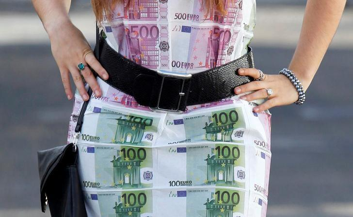 A woman wears a home-made dress featuring imitation 100 and 500 euro notes as she walks in Bordeaux, southwestern France, November 7, 2014. REUTERS/Regis Duvignau/File Photo