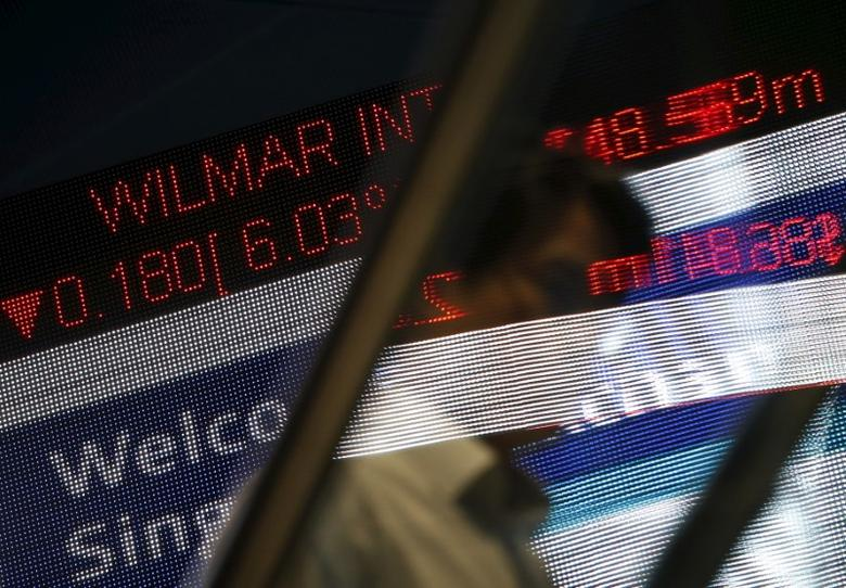 A man passes a stock index board showing Wilmar International losing 6.03 percent at the Singapore Exchange in the central business district August 24, 2015.  REUTERS/Edgar Su