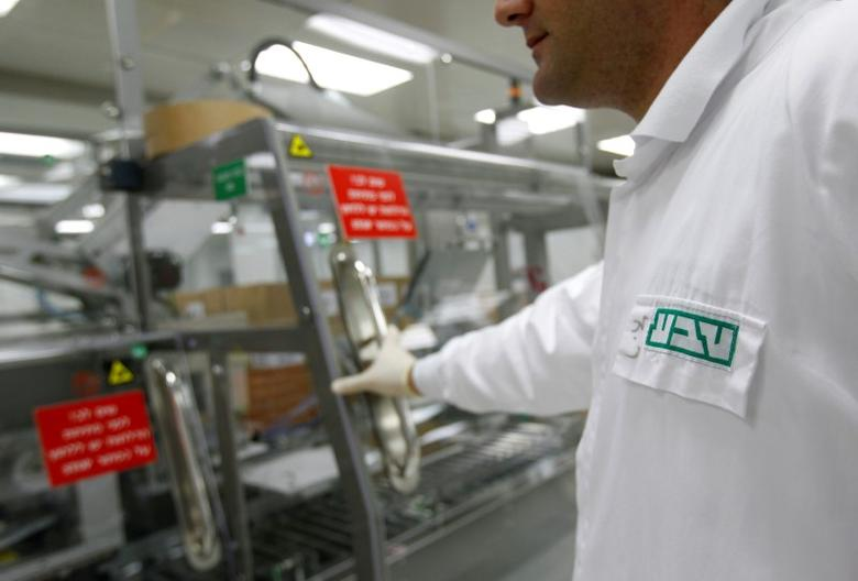 FILE PHOTO: An employee of Teva Pharmaceutical Industries wears a shirt bearing the company's logo at its Jerusalem oral solid dosage plant (OSD) December 21, 2011.  REUTERS/Ronen Zvulun/File Photo
