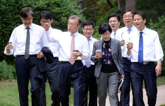South Korean new President Moon Jae-in talks with senior presidential secretaries as they take a walk at the Presidential Blue House in Seoul, South Korea May 11, 2017.  Kim Joo Hyung/Yonhap via REUTERS