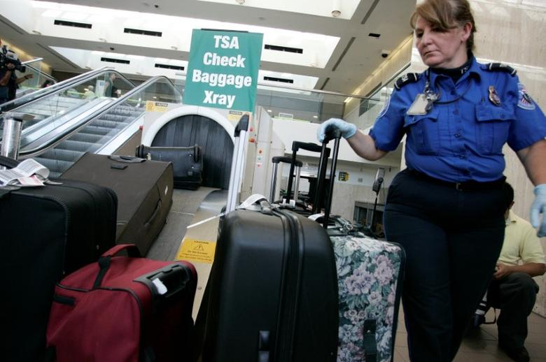 A TSA worker loads suitcases at the checked luggage security screening station at Los Angeles International Airport in Los Angeles, California, U.S. on September 7, 2011. REUTERS/Jonathan Alcorn/Files