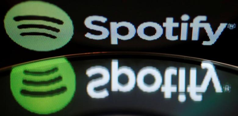 The logo of online music streaming service Spotify is reflected in an audio music CD in this February 18, 2014 illustration picture. REUTERS/Vincent Kessler/File Photo