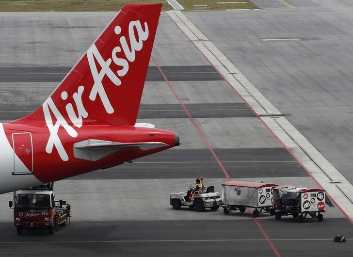 An AirAsia baggage handler drops a bag on the tarmac at Kuala Lumpur International Airport in Sepang, Malaysia, June 17, 2015. REUTERS/Olivia Harris